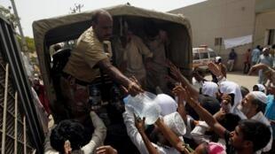 Soldados distribuem água para população em Karachi, no Paquistão.