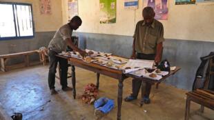 Le 31 octobre, dans le Fokontany, dans le quartier de Tanambe à Amboasary, le chef adjoint classe les quelque 1000 cartes d'électeurs reçues, pendant que les citoyens viennent consulter les listes électorales.