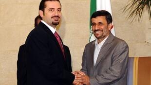 El presidente Mahmud Ahmadinejad (derecha) estrecha las manos del primer ministro libanés Saad Hariri.