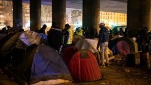 Des migrants et réfugiés rassemblent leurs affaires pour évacuer le campement sous le pont entre la Porte de la Villette et la Porte de la Chapelle, le 31 janvier 2019. Cette opération est la quatrième permettant à 800 migrants de trouver un abri.