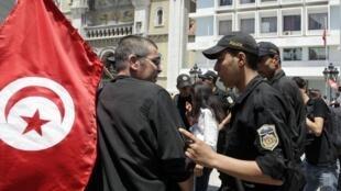 Un policier anti-émeutes s'adresse à un manifestant, lors d'un rassemblement anti-gouvernemental avenue Bourguiba, à Tunis, le 2 juin 2012.