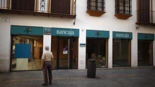 Cliente diante de uma agência bancária em Málaga, interior da Espanha.