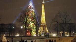 Pessoas passeando no jardim do Tuileries com vista para as iluminações de natal no pinheiro de natal e para a Torre Eiffel.