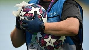 A member of the ground staff disinfects a ball before the Champions League last 16 match between Manchester City and Real Madrid at the Etihad Stadium in Manchester on August 7