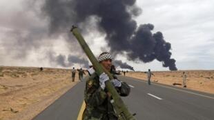 Ливийский повстанец с переносным противовоздушным комплексом на дороге между Рас-Лануфом и Бен-Джавадом 9 марта 2011 года. Четыре дня спустя и Рас-Лануф, и Бен-Джавад находятся в руках сил Каддафи