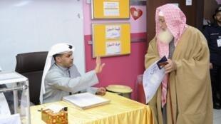 Un électeur koweitien tient sa carte de vote et sa carte de nationalité, à un kiosque de vote pour les élections parlementaires à Jahra, au Koweït le 2 février 2012.