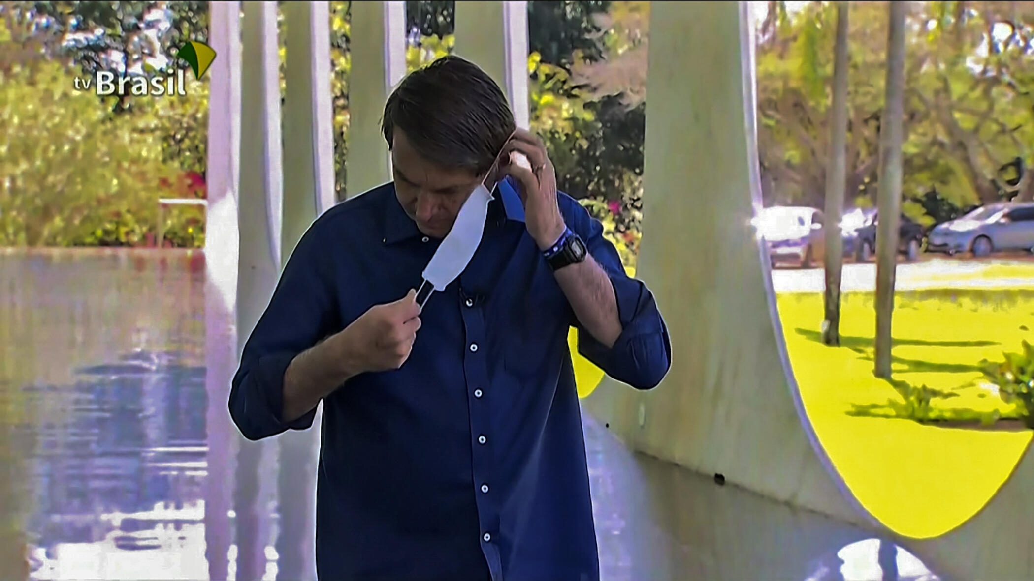 A screen grab from TV Brasil shows Brazilian President Jair Bolsonaro putting a face mask on as he prepares to speak with journalists at Planalto Palace in Brasilia on July 7, 2020. He later removed it.