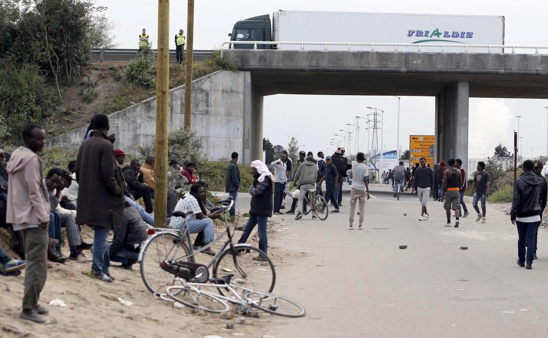 Migrantes vigiados pelas forças policiais junto do Eurotúnel, na zona de Calais a 19 de Agosto de 2015.
