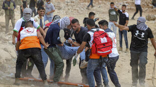 Palestinian protesters help a man who was wounded during clashes with the Israeli army in the village of Beita in the occupied West Bank