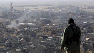 Membro das forças curdas observa a cidade de Sinjar, antes controlada pelo EI.