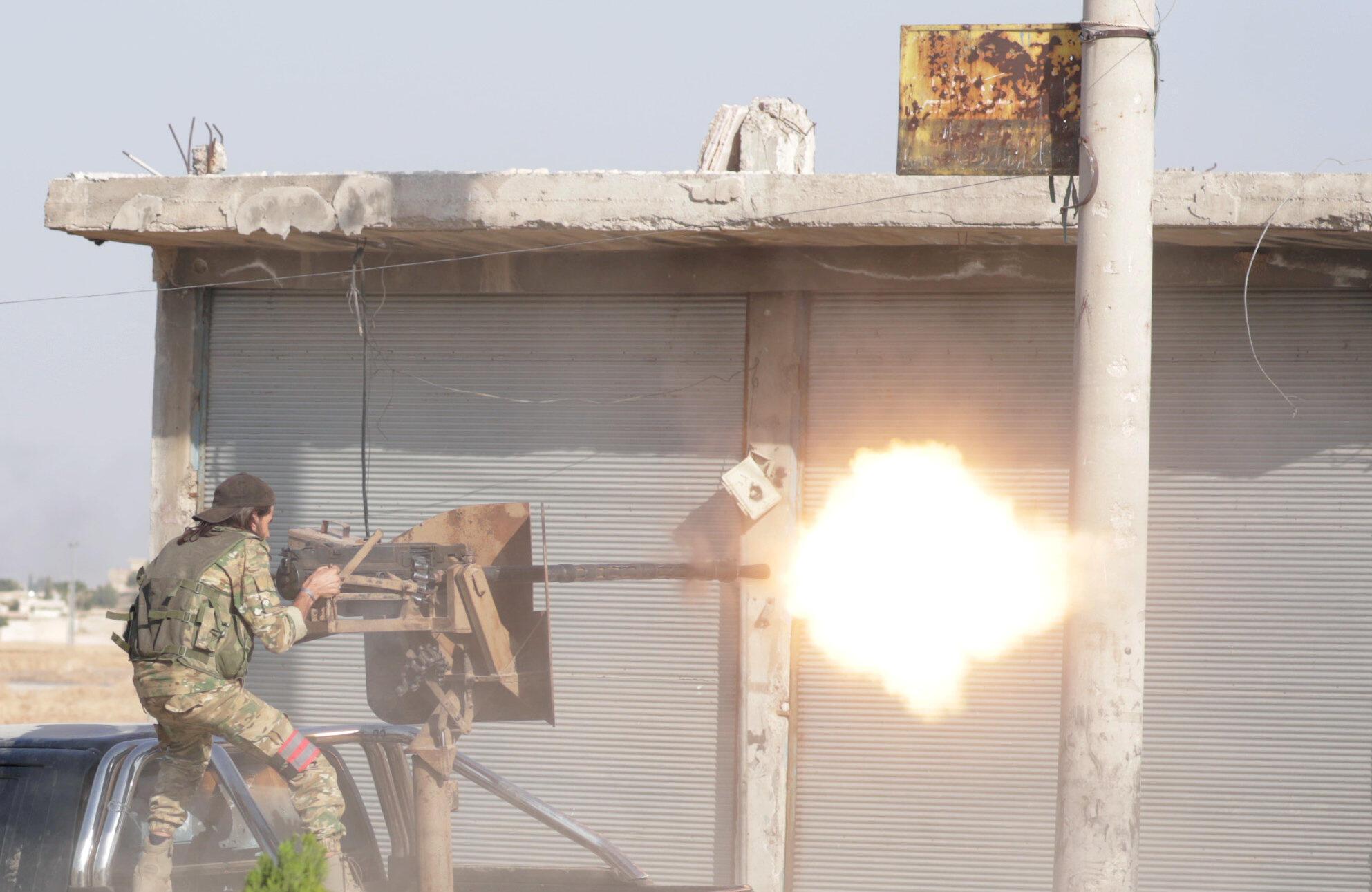 Combatente rebelde sírio apoiado pela Turquia dispara uma arma na cidade de Tal Abyad, Síria, 13 de outubro de 2019.