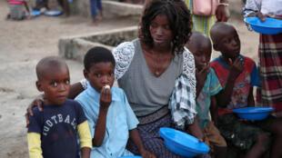 Crianças se alimentam em centro de acolhimento de vítimas do ciclone Idai, em Beira, Moçambique.