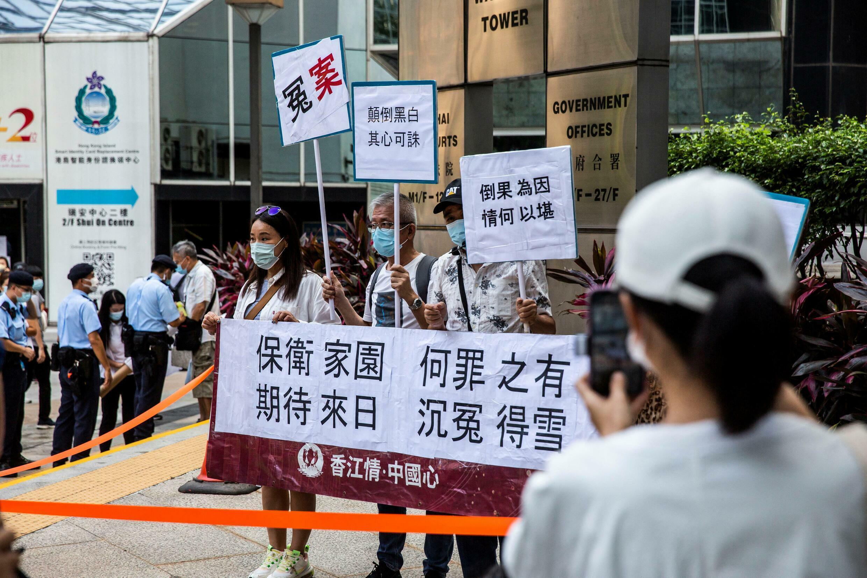 Les partisans des accusés tiennent des pancartes devant le tribunal de district de Wanchai à Hong Kong le 22 juillet 2021.