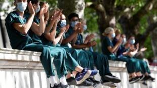 Des agents de santé applaudissent devant l'hôpital St Thomas à l'occasion du 72e anniversaire du NHS, en pleine épidémie de coronavirus, à Londres, Grande-Bretagne, le 5 juillet 2020.