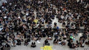 Des manifestants assis dans le hall des arrivées à l'aéroport de Hong Kong, le 26 juillet 2019.