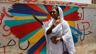 Alaa Salah, icône de la révolution au Soudan, pose devant une peinture murale la représentant, en face du ministre de la Défense à Khartoum, le 20 avril 2019.