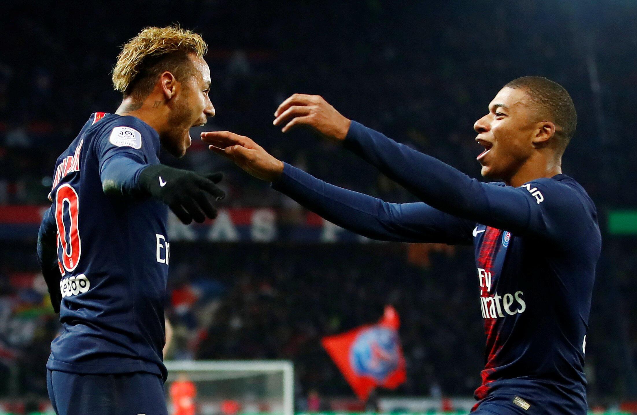 Neymar (esquerda), avançado brasileiro do PSG, e Kylian Mbappé (direita), avançado francês do PSG, festejam o 12° triunfo dos parisienses.