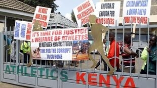 Protesting Kenyan athletes place placards behind closed gates at Riadha House the Athletic Kenya (AK) Headquarters in capital Nairobi November 23, 2015.