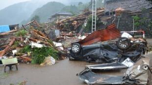 Um carro entre casas destruídas na cidade de Minamiaso, após as chuvas torrenciais que atingem o Japão há três dias.