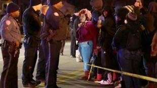 Des personnes font part de leur colère auprès d'agents de police qui maintiennent une périmètre de protection autour de la scène de crime où un jeune homme a été tué mardi 23 décembre 2014 par un officier à Berkeley, dans le Missouri.