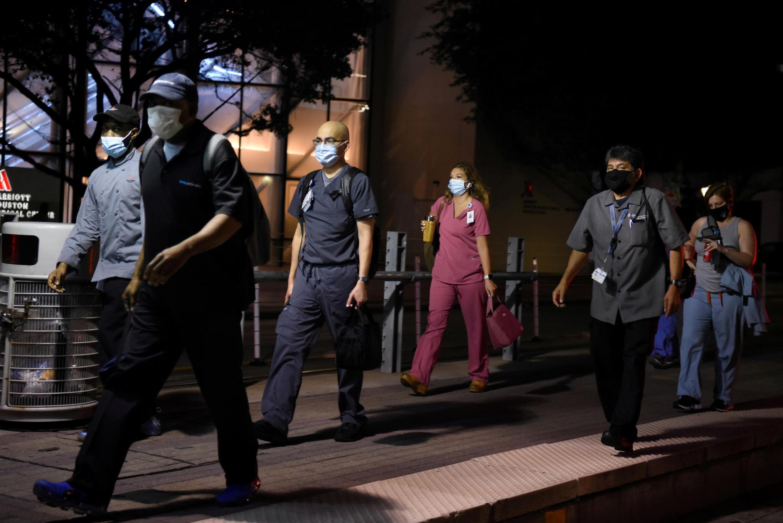 Des travailleurs de la santé traversent le Texas Medical Center lors d'un changement de poste à Houston, le 8 juillet 2020.