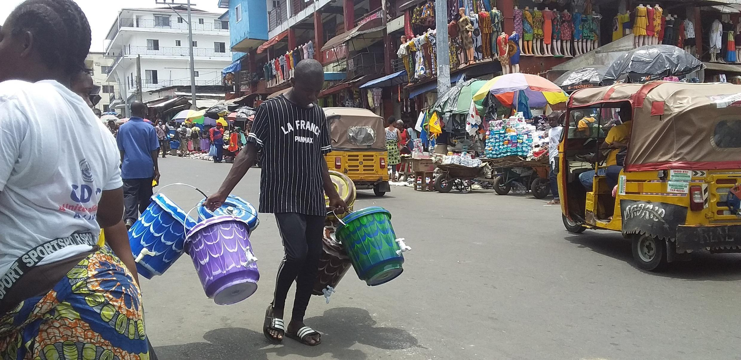 A man selling buckets at premium prices in downtown Monrovia, Liberi