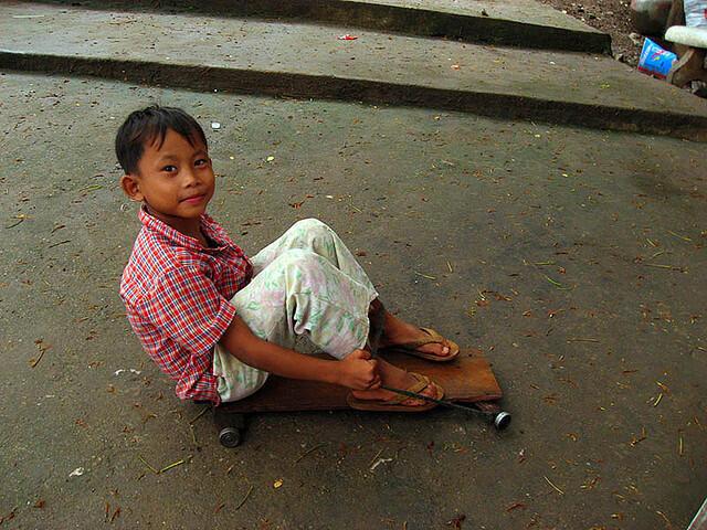 Boy riding homemade skateboard in Cambodia