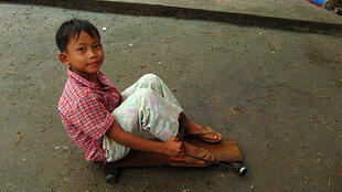 Boy riding homemade skateboard in Cambodia