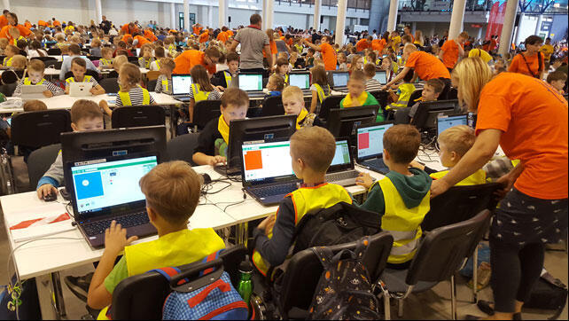 De jeunes élèves absorbés par leur défi informatique.