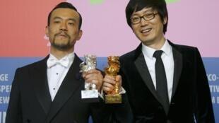 """Diao Yinan (direita), diretor de """"Bai Ri Yan Huo"""" (""""Carvão negro, gelo fino"""") posa ao lado do ator Liao Fan (esquerda), eleito o melhor ator na Berlinale."""