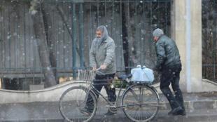 Moradores de Damasco carregam garrafão de água nas ruas da capital.