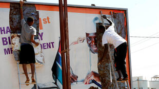 Des Gambiens détachent un poster de l'ancien président Yahya Jammeh, le 4 décembre 2016.