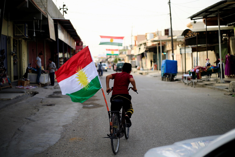 Мальчик с курдским флагом на улице города Туз Хурмато в иракском Курдистане. 24 сентября 2017 года.