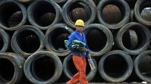 Un ouvrier passe devant des bobines d'acier d'une usine de Shenyang, dans la province du Liaoning en Chine.