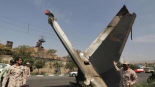 Membros das forças de segurança ao lado da cauda do avião, no meio de uma rua de Teerã