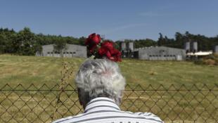 Un Rom tenant une fleur devant les barrières de la porcherie industrielle situé sur le site du camp de concentration de Lety en juin 2017.