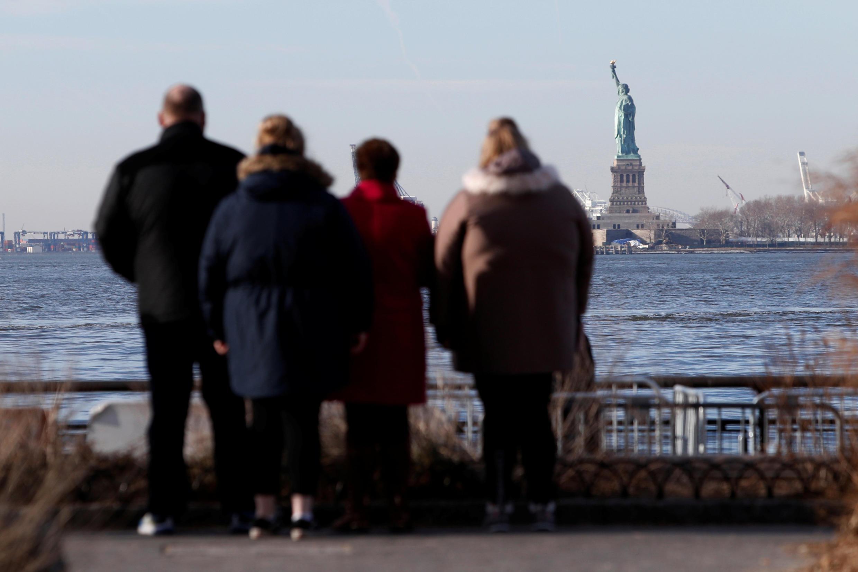 گردشگران دورادور مجمسۀ آزادی در ساحل نیویورک را تماشا میکنند ـ  ژانویۀ ٢٠١٨