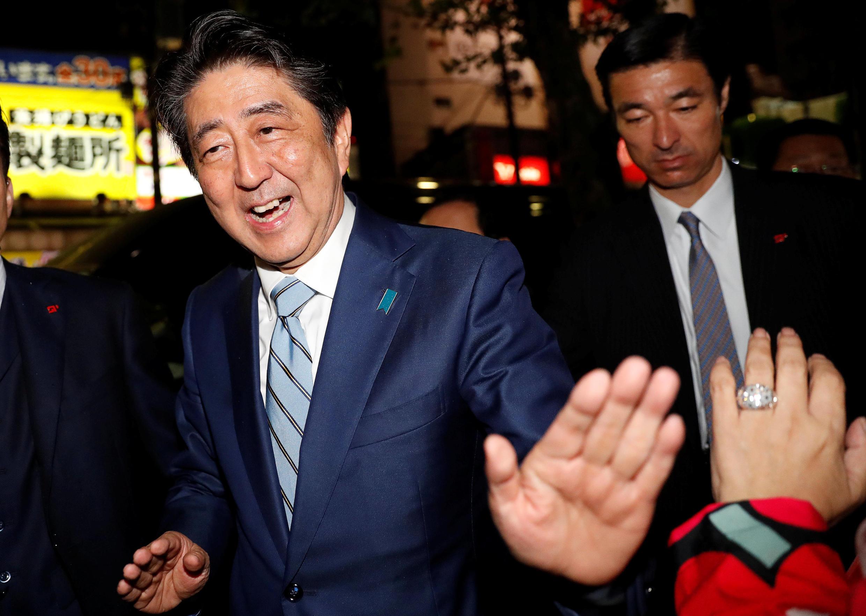 Em primeiro plano, o primeiro-ministro japonês, Shinzo Abe, participa de comício em Tóquio no dia 20 de outubro.