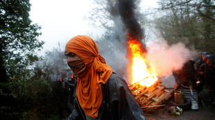 A protestor walks past burning debris as French gendarmes continue to clear Notre-Dame-des-Landes protest camp, near Nantes on 9 April 2018.