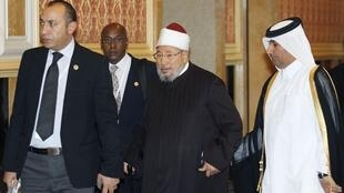 Sheikh Yusuf al-Qaradawi (C) arrives at the opening of the International Conference on Jerusalem in Doha