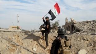 Um membro das forças de segurança do Iraque ergue uma bandeira iraquiana na cidade de Ramadi, 27 de dezembro de 2015.