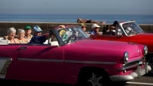 Des touristes circulent dans une vieille voiture cubaine, sur le front de mer de La Havane, le 15 mars 2016.