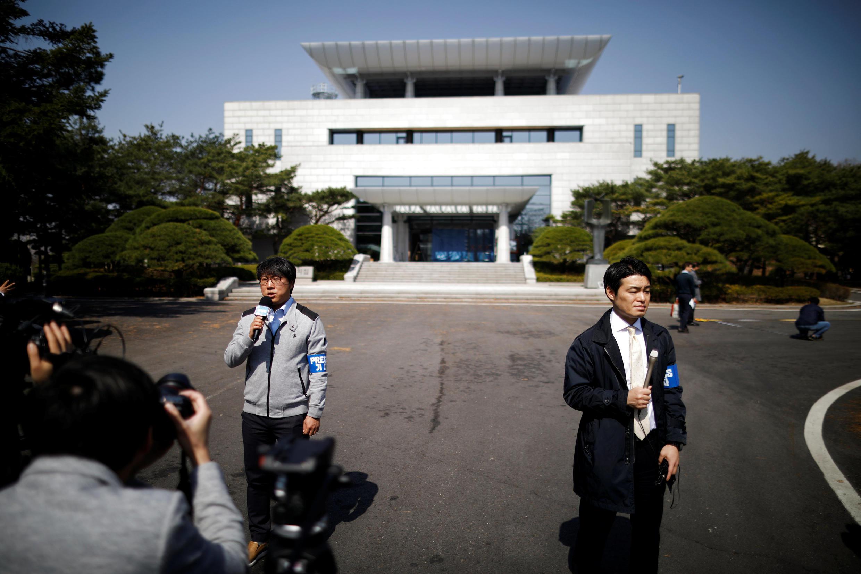 Les médias font un reportage devant la Maison de la paix au village trêve de Panmunjeom à l'intérieur de la zone démilitarisée séparant les deux Corées, en Corée du Sud, le 18 avril 2018.