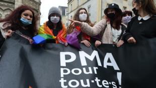 """Manifestantes con un cartel que dice """"PMA (reproducción asistida) para todos"""",  durante una protesta contra el proyecto de ley de bioética, el 30 de enero de 2021, en Angers, Francia"""