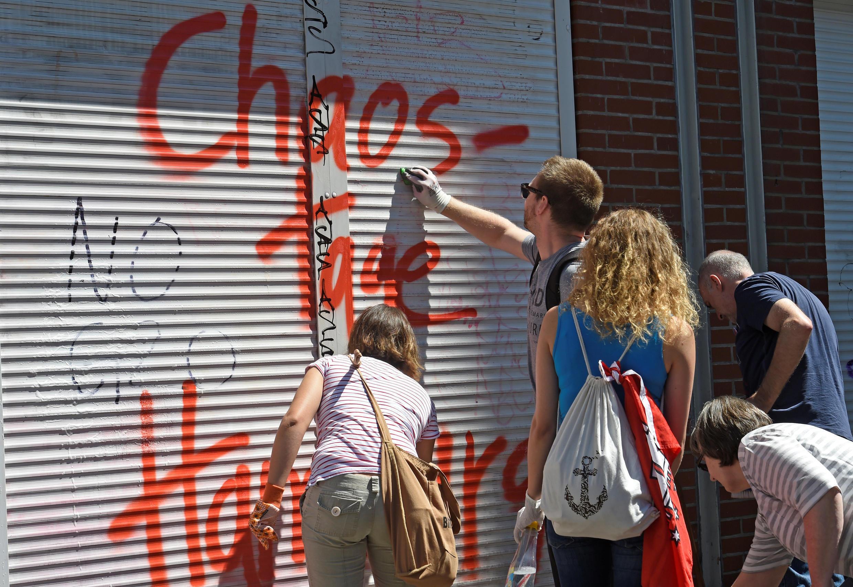 Des résidents néttoient la devanture d'une boutique fermée, avec l'inscription « Les jours de Chaos de Hambourg », après les manifestations lors du sommet du G20, dans le quartier de Sternschanze à Hambourg, en Allemagne, le 9 juillet 2017.