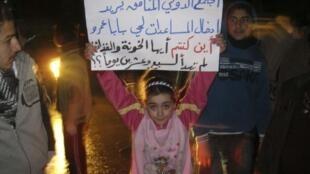 Cette fillette de Homs, dont le père aurait été tué dans les bombardements de Bab Amro, prend à partie, sur sa pancarte, la communauté internationale pour sa passivité, le 3 mars 2012.