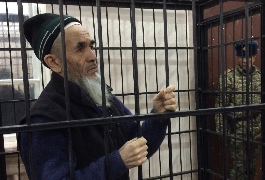 Azimjan Askarov (66 ans) dans une cage lors d'un procès entaché d'irrégularités, condamné à la prison à vie en 2010, peine confirmée en appel par un tribunal régional fin janvier 2017.