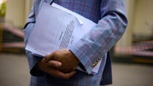 El abogado Ivan Pavlov con documentos mientras habla a los medios a las afueras del tribunal de Moscú, en Rusia, el 17 de mayo de 2021