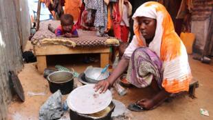 Beaucoup de personnes ont fui les zones touchées par la sécheresse dans la région du Bas-Shabelle prépare le repas de sa famille au camp d'al-Adala pour personnes déplacées, juste à l'extérieur de la capitale somalienne, Mogadiscio, le 15 mai 2019.