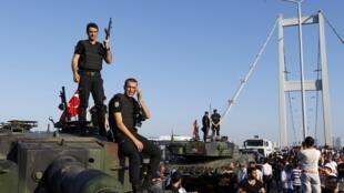 Les policiers se tiennent sur l'un des véhicules blindés de l'armée après que les troupes impliquées dans le coup d'État se sont rendus sur le pont du Bosphore à Istanbul, le 16 juillet 2016.